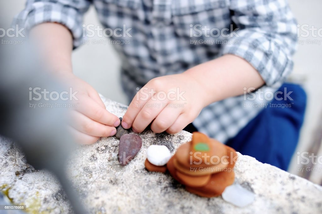 Cute blonde little boy playing with little stones outdoors royalty-free stock photo