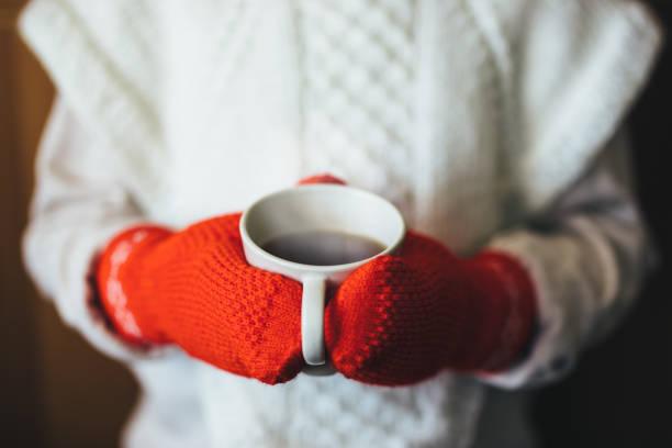 cute blonde little girl holding hot steaming tea cup close up photo - mitene imagens e fotografias de stock