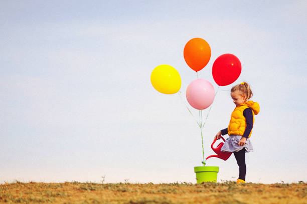 Cute blonde little girl is seeding and watering colorful balloons stock photo