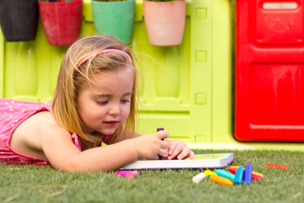A cute blonde little girl laying on the grass and colouring a book. There is a colorful toy house on the background and some crayons on the grass. stock photo