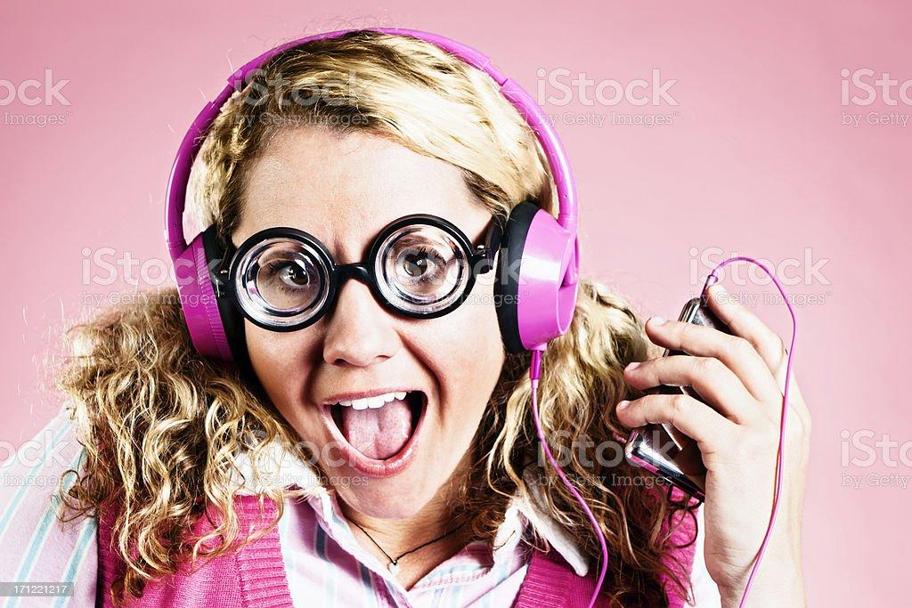 Cute blonde nerd gets her groove on in pink headphones royalty-free stock photo