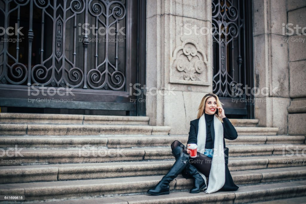 Cute blonde relaxing on steps stock photo
