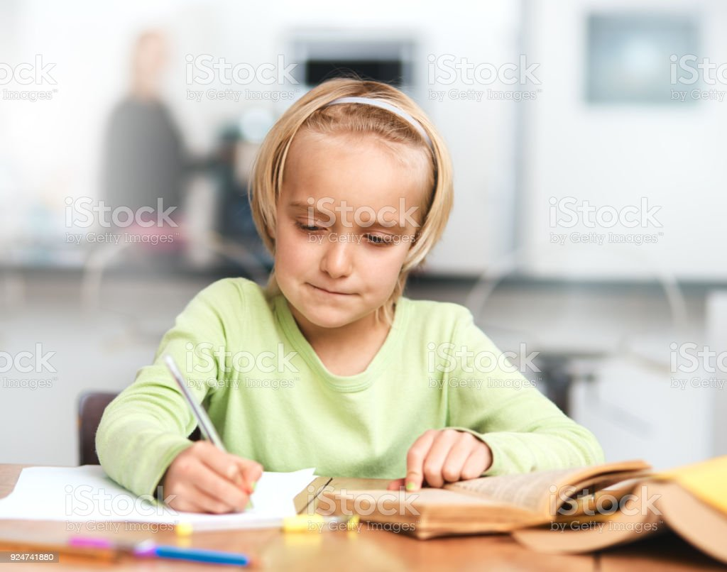 Cute Blonde Schoolgirl Concentrating On Her Homework Royalty Free Stock Photo