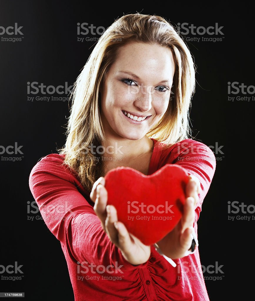 Cute blonde symbolically offers her heart stock photo