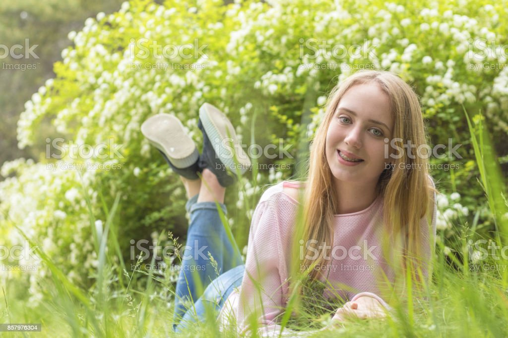 Cute blonde teenage-girl dreaming on a sunny day on the grass stock photo