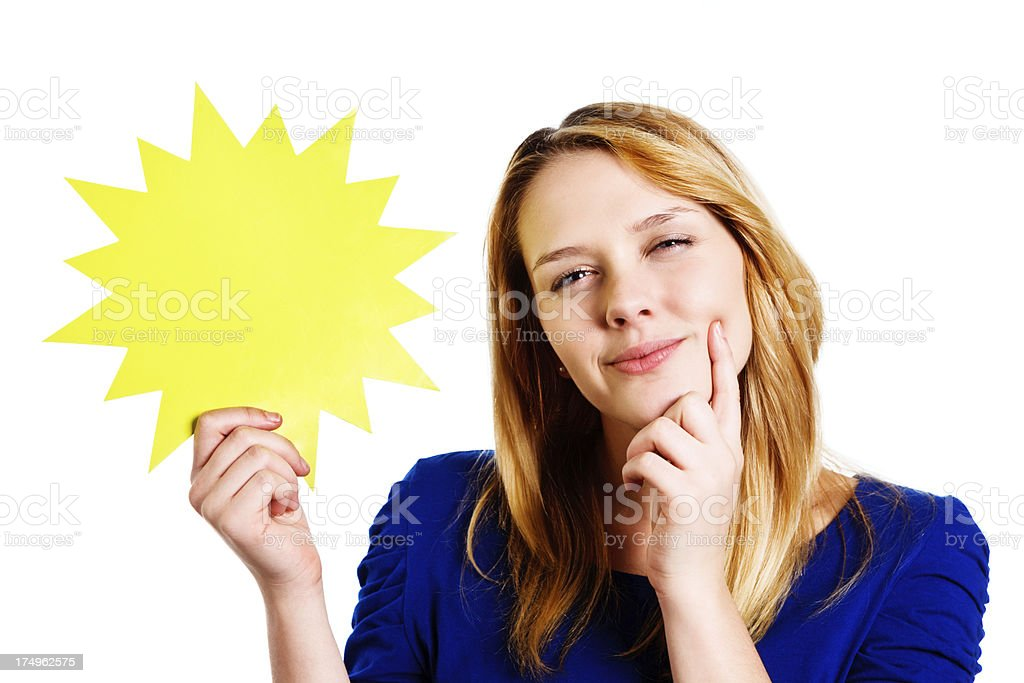 Cute blonde teenager considers blank sign she holds, smiling royalty-free stock photo