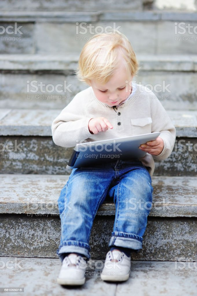 Cute blonde toddler boy playing with a digital tablet outdoors royalty-free stock photo