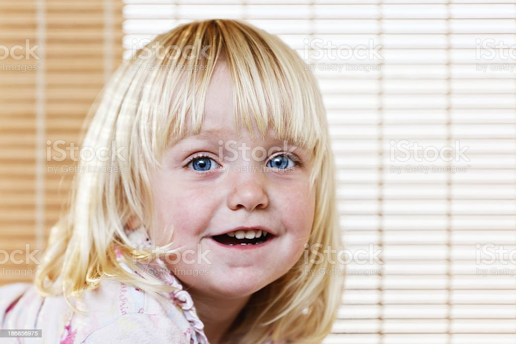 Cute blonde two year old girl smiles by venetian blinds stock photo
