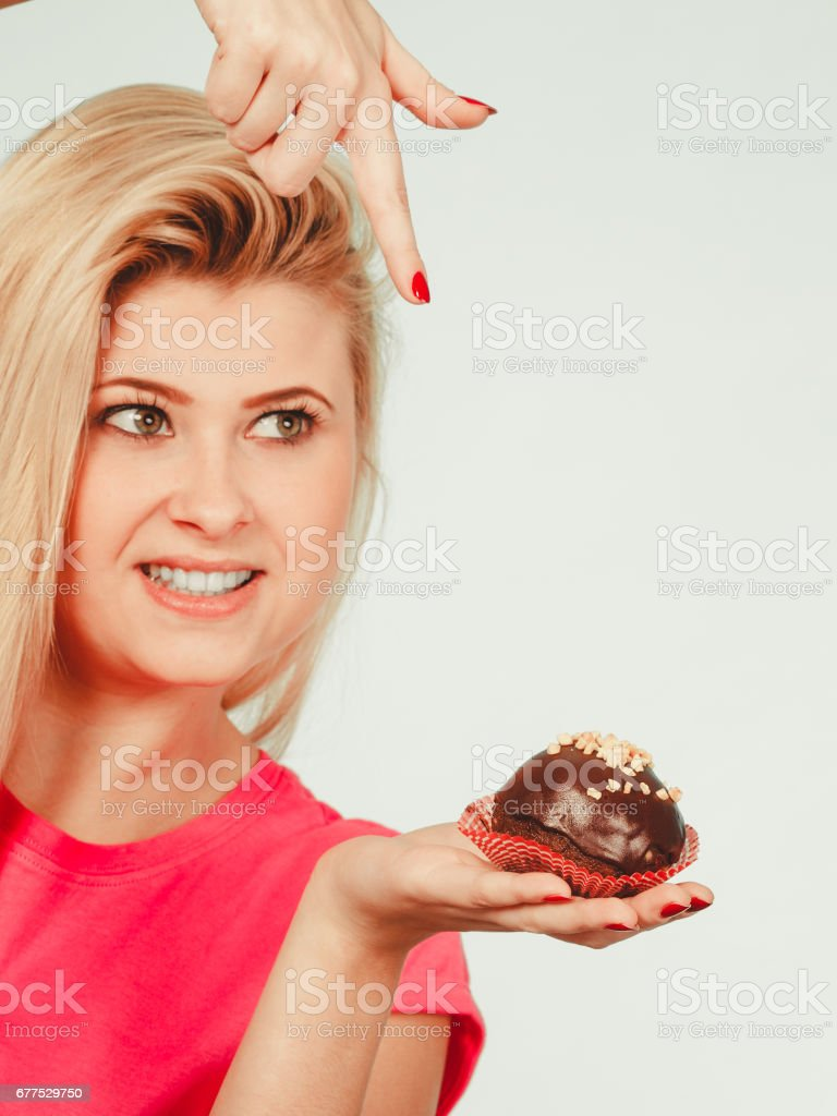Cute blonde woman about to eat cupcake royalty-free stock photo