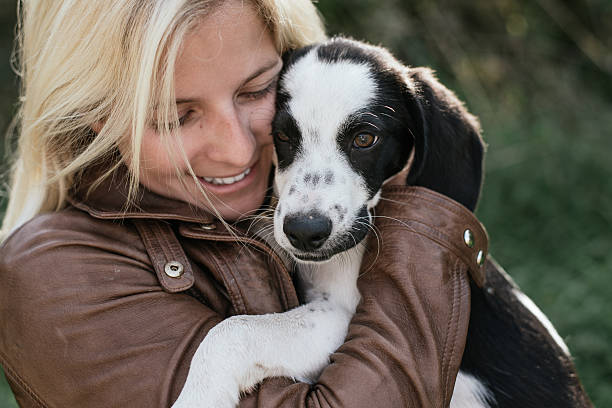 Cute blonde woman and her puppy playing outdoor stock photo