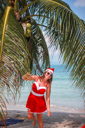 1155046257 istock photo Cute blonde woman in red dress, sunglasses and santa hat 615916814