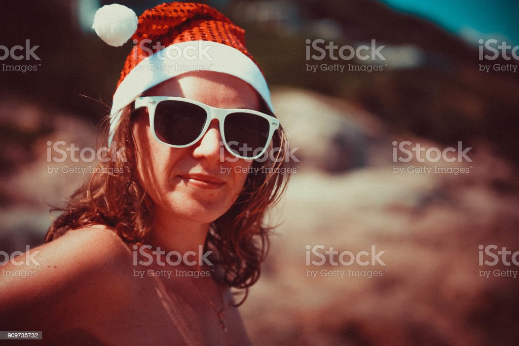 4a1e5b26 Cute blonde woman in sunglasses and santa hat on at exotic tropical beach  in retro colors