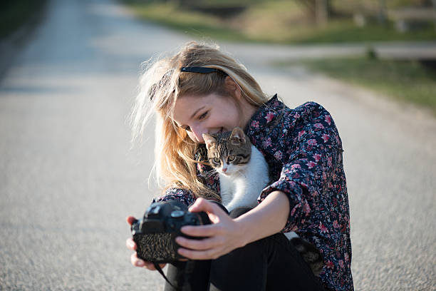 Cute blonde woman taking self portrait with a cat stock photo
