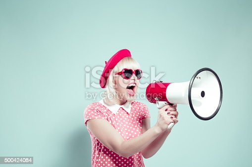 Portrait of excited blonde young woman wearing pink dotted dress, red beret and heart shaped sunglasses, shouting into megaphone. Studio shot, one person, turquoise background.