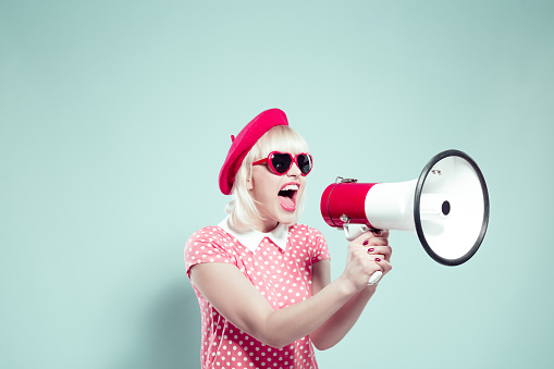 Cute blonde young woman shouting into megaphone