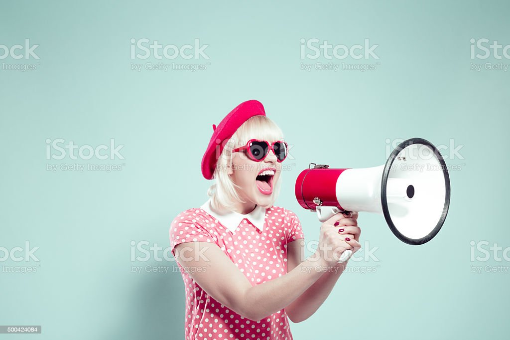 Cute blonde young woman shouting into megaphone stock photo