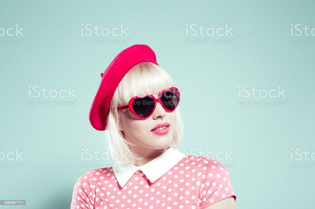 Cute blonde young woman wearing heart shaped sunglasses stock photo
