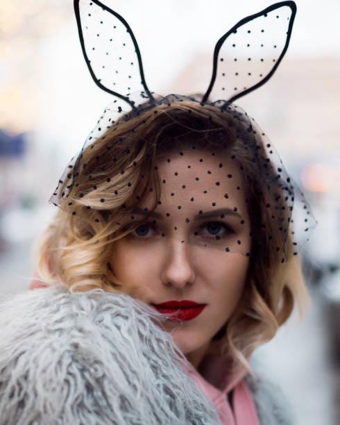 niedliche blondie mädchen mode kunstpelz mantel und schwarzen schleier mit hasenohren und rote lippen draußen winter. - coole halloween kostüme stock-fotos und bilder