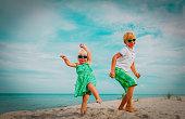 cute happy boy and girl dance at beach, happy kids enjoy vacation at sea