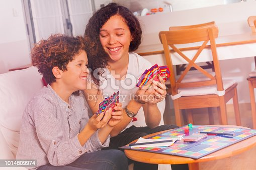 istock Cute boy and girl having fun playing tabletop game 1014809974
