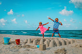 cute boy and girl play with sand, kid building castle on beach vacation