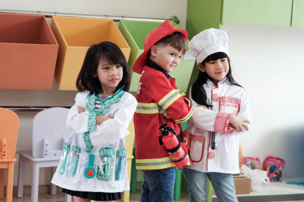 Cute boy and girls playing as fireman, doctor and cook occupation in kindergarten class, kid occupation, education concept Cute boy and girls playing as fireman, doctor and cook occupation in kindergarten class, kid occupation, education concept dressing up stock pictures, royalty-free photos & images