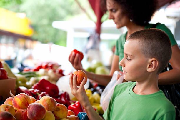 carino ragazzo e sua madre presso il farmer's market - pesche bambino foto e immagini stock