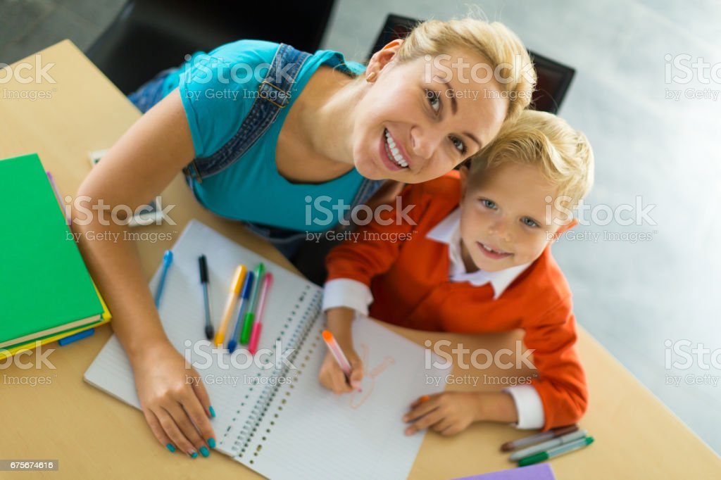 Cute boy and his mom sit at the desk in the office and hold pencils royalty-free stock photo