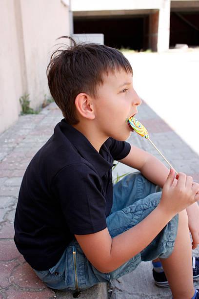 Cute boy and lollipop stock photo