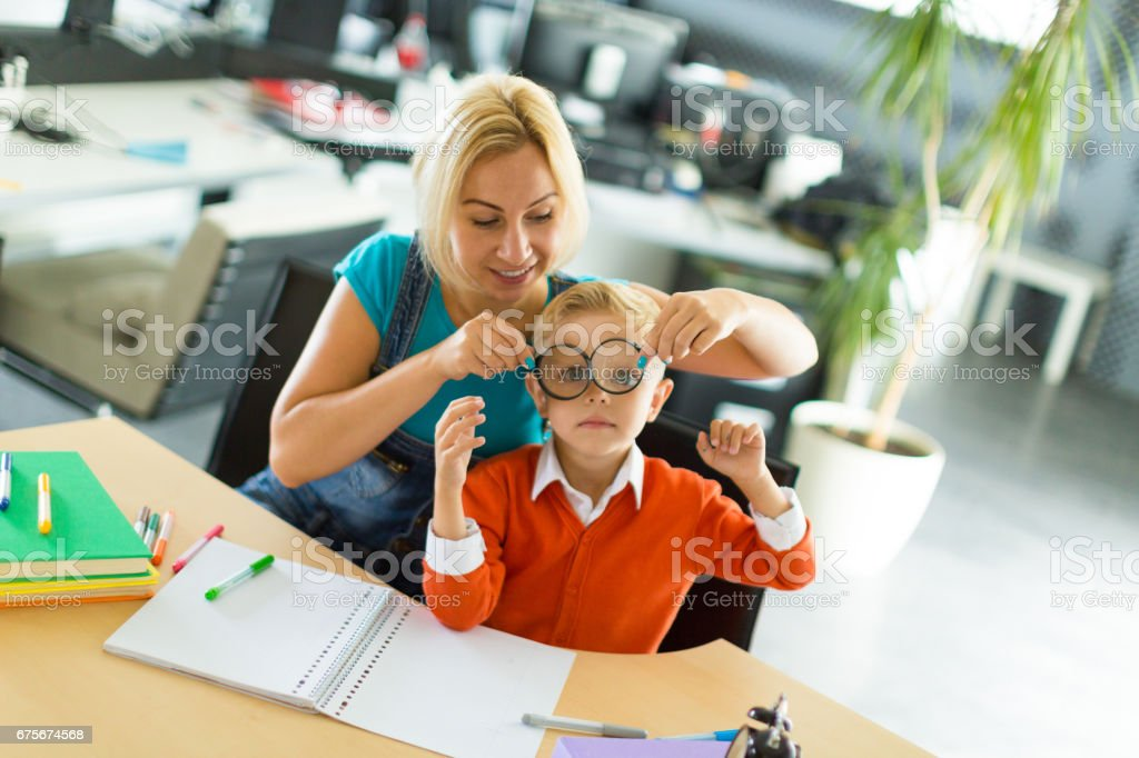 Cute boy and woman sit at the desk in the office and play royalty-free stock photo
