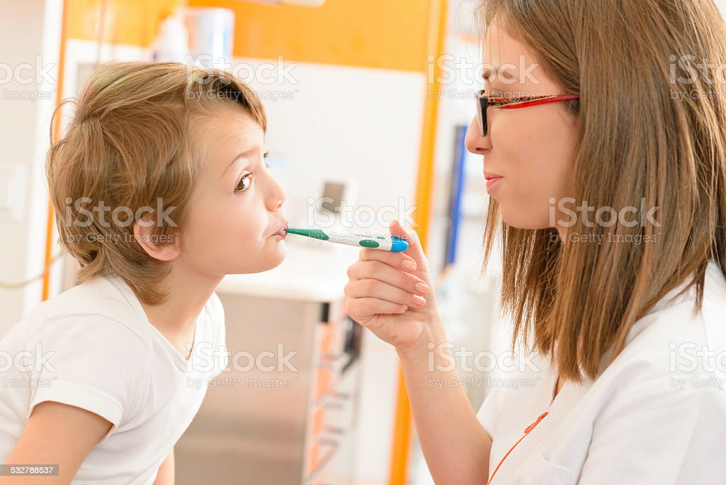 Cute boy being checked at clinic stock photo