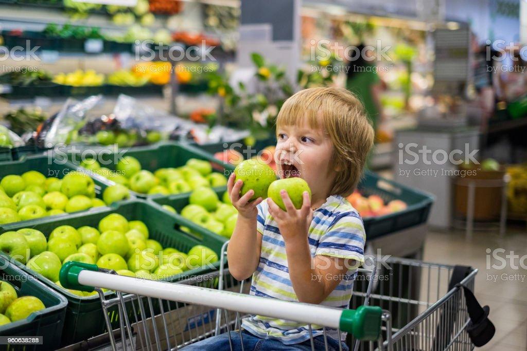 Garoto bonito mordendo dois apple na loja - foto de acervo