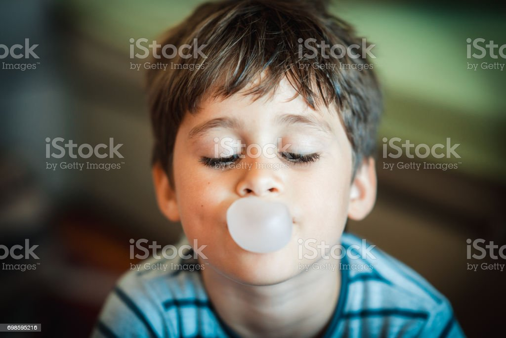 Cute boy blowing bubble gum stock photo