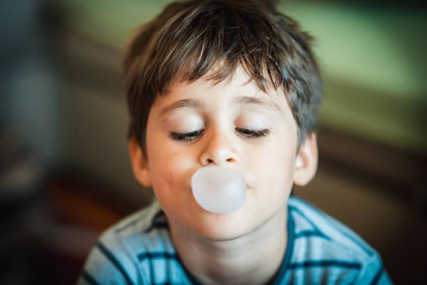 Cute boy blowing bubble gum stock photo