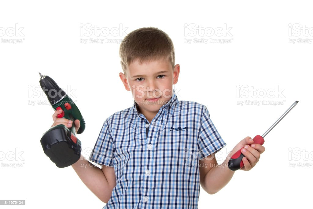 A cute boy builder in checkered shirt demonstrates the difficulty of choosing a screwdriver, isolated on white background stock photo