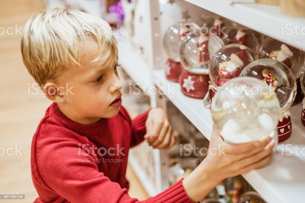 Cute boy chosing christmas decoration stock photo