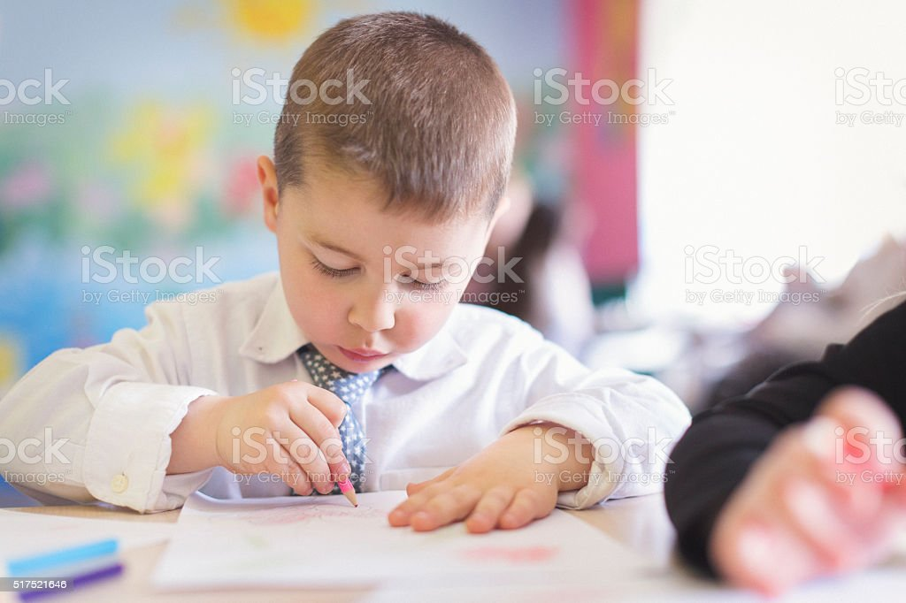 Cute boy drawing in the classroom stock photo