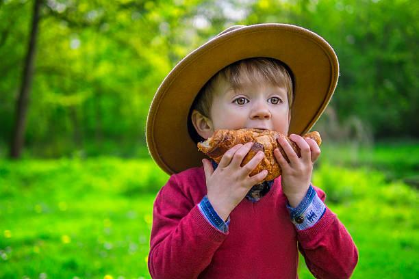 Süße junge Essen ein croissant – Foto