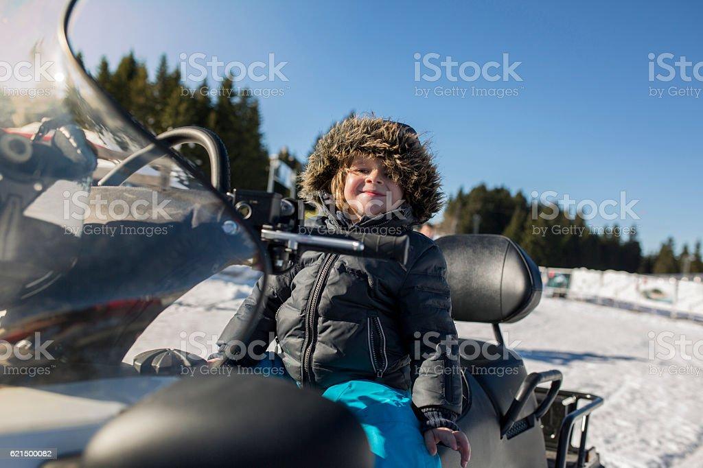Cute boy enjoying in winter day on a snowmobile. foto stock royalty-free