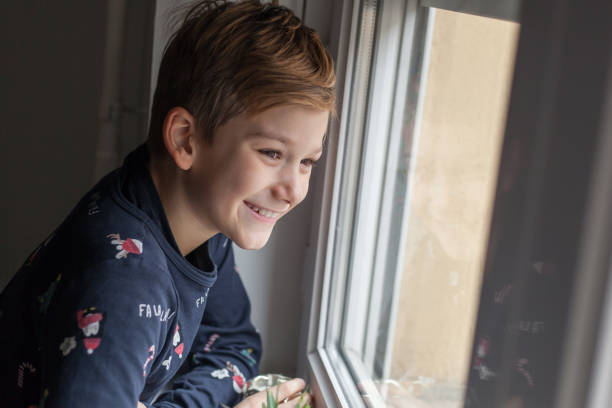 Cute boy enjoying while looking through window. Happy boy day dreaming while looking through window. boy looking out window stock pictures, royalty-free photos & images