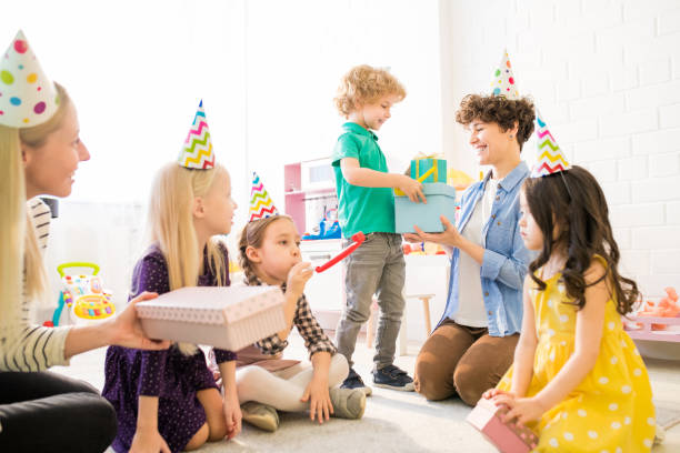 Cute boy giving gift boxes to mother at birthday party Smiling cute boy in green polo tshirt standing at curly-haired mother and giving gift boxes to her at birthday party, other children waiting for their turn to congratulate birthday boy group of friends giving gifts to the birthday girl stock pictures, royalty-free photos & images