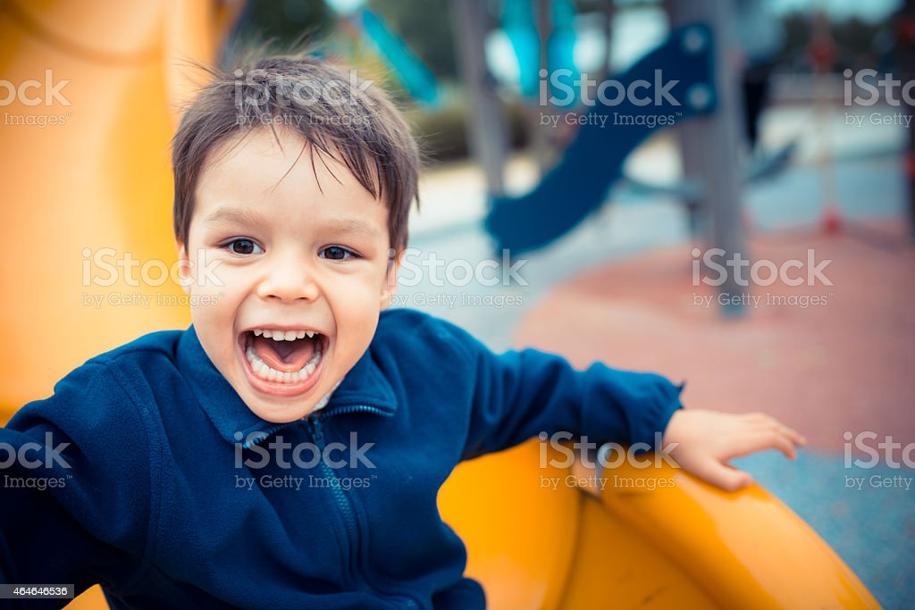 Cute boy happily playing on a playground slide stock photo