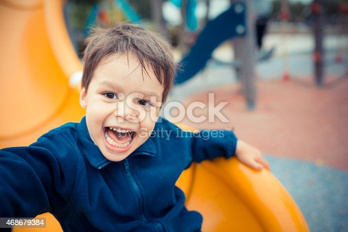 istock Cute boy happily playing on a playground slide 468679384