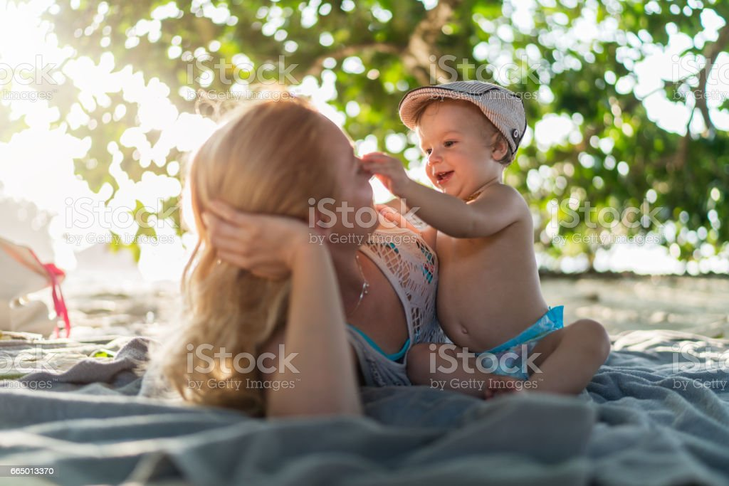 Cute boy having fun with his mother on the beach. stock photo