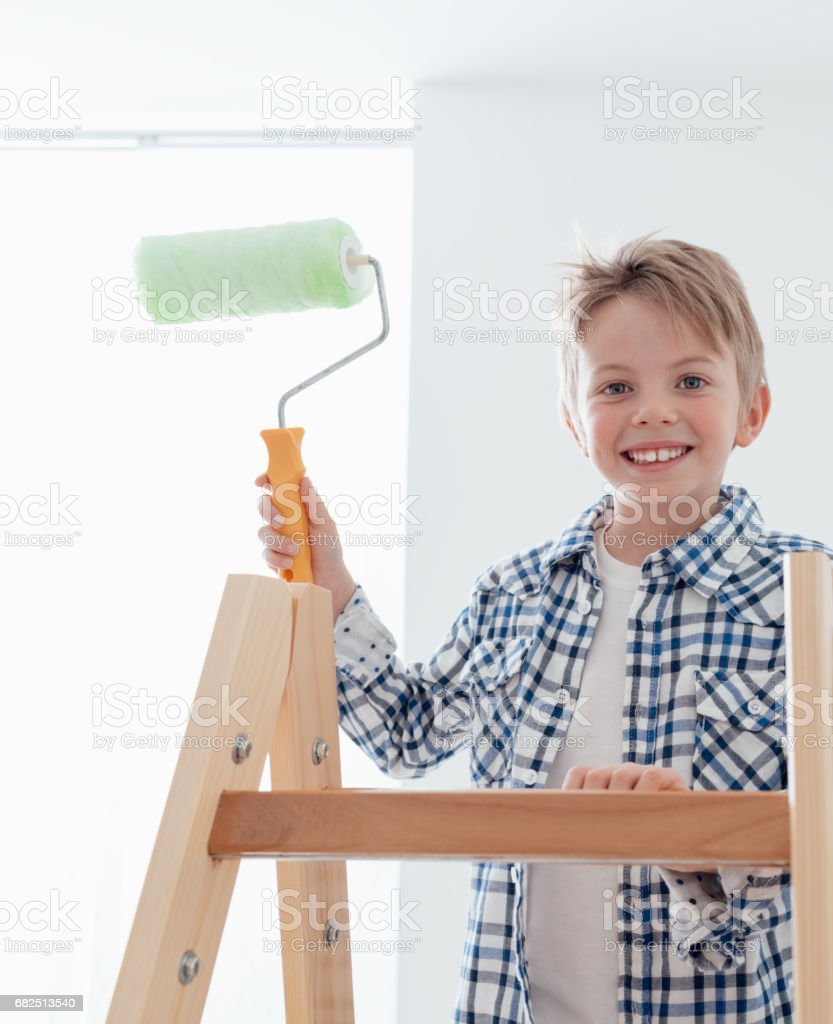 Cute boy holding a paint roller royalty-free stock photo