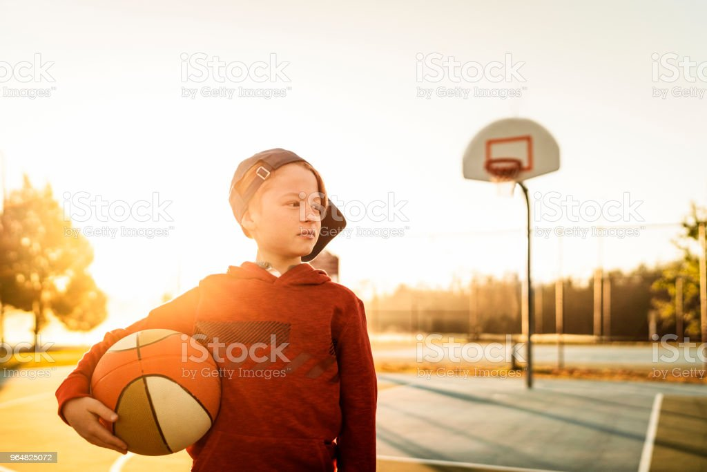 Cute boy holding basketball at court royalty-free stock photo