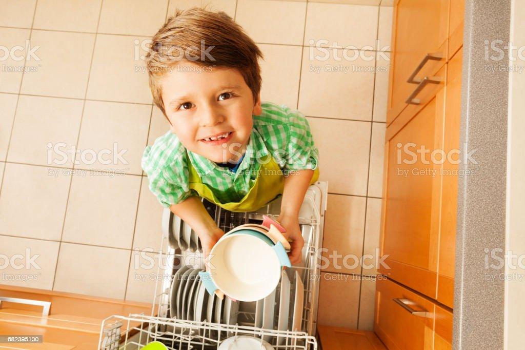 Bols de mignon garçon tenant debout à côté du lave-vaisselle photo libre de droits