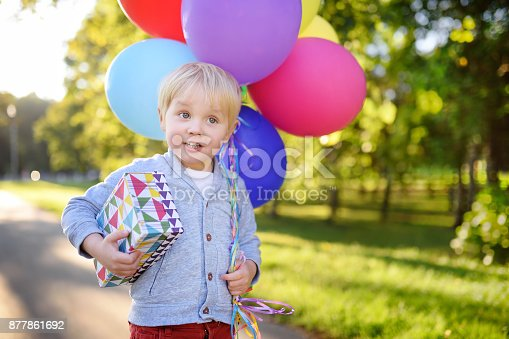 istock Cute boy holding bundle of colorful balloons and gift in a festive box. Happy Birthday! 877861692
