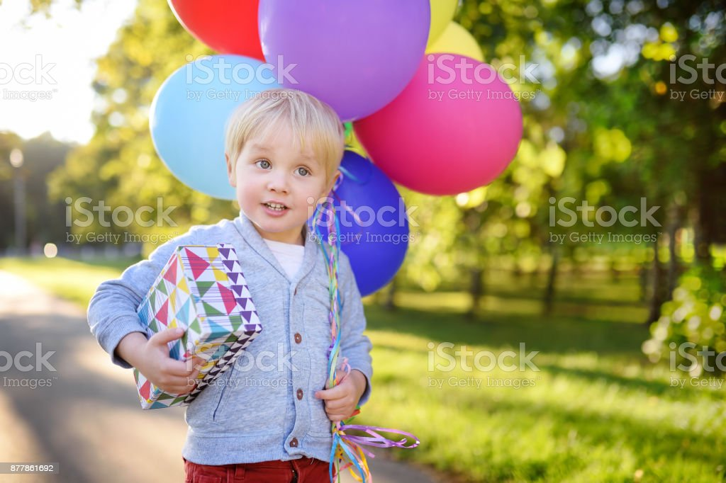 Cute boy holding bundle of colorful balloons and gift in a festive box. Happy Birthday! stock photo