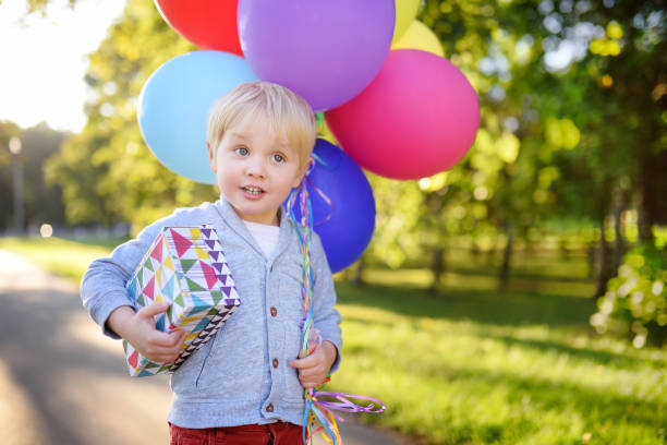 cute boy holding bundle of colorful balloons and gift in a festive box. happy birthday! - birthday gift stock photos and pictures
